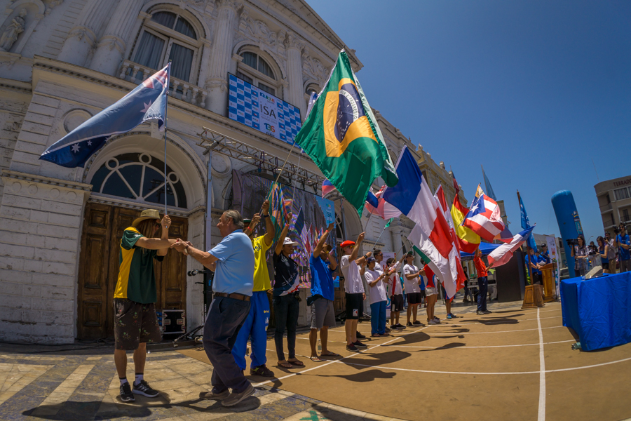 A representative from each National Delegation takes to the stage waving their flags. Photo: ISA/Sean Evan