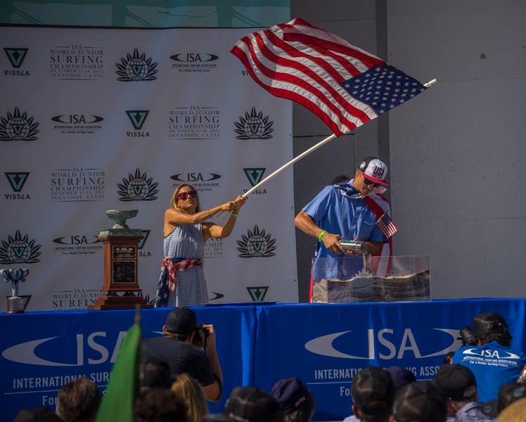 El portador de la arena, Colt Ward, y la portadora de la bandera, Tia Blanco, vuelcan la arena de la Playa de Oceanside. Foto: ISA/Sean Evans
