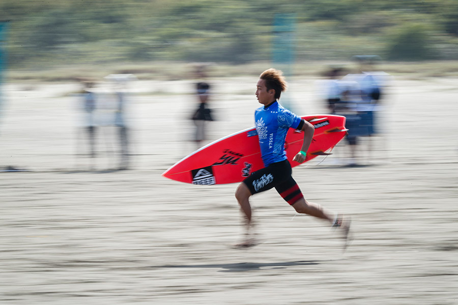 Joh Azuchi sprints into Japan's final leg of the relay. Photo: ISA / Ben Reed