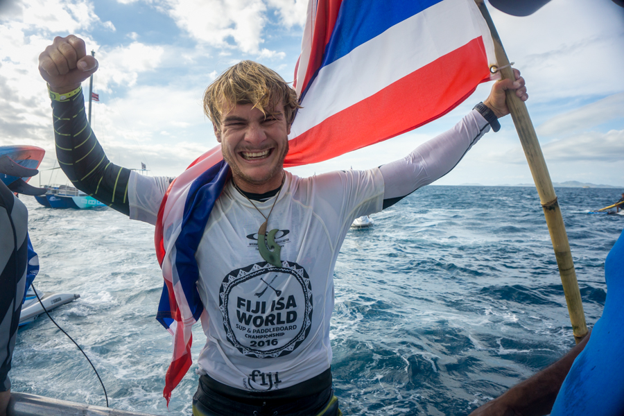 After a day of epic Cloudbreak, Zane Schweitzer holds his flag high as World Champion. Photo: ISA / Sean Evans